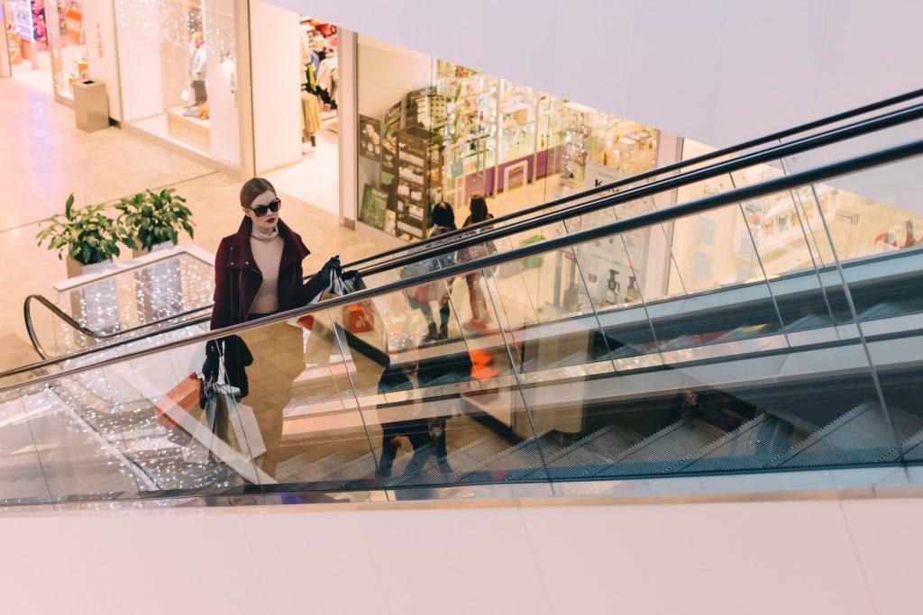 Lady riding escalator in mall.