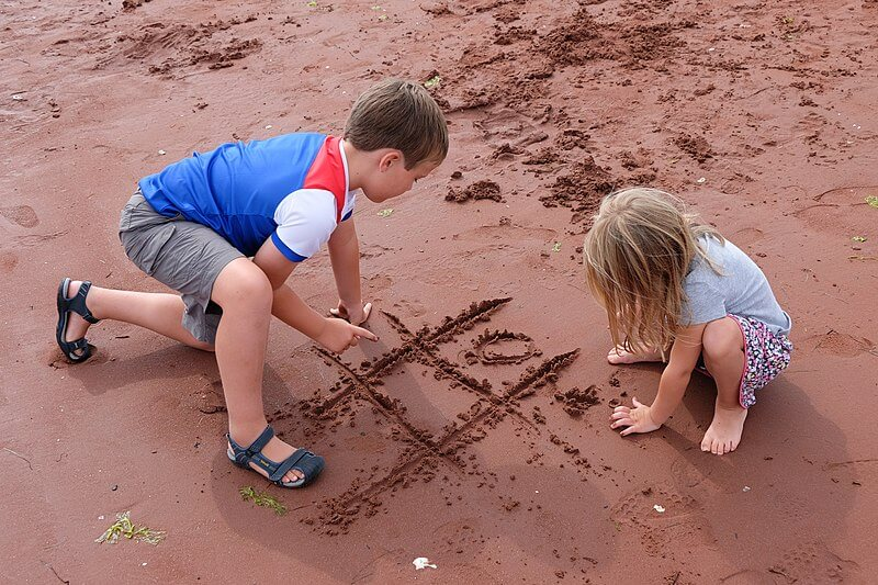 Children playing tic-tac-toe on the beach
