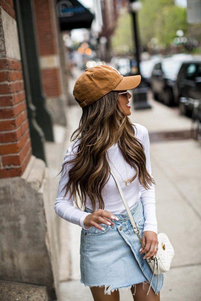 Girl wearing denim skit with ball cap