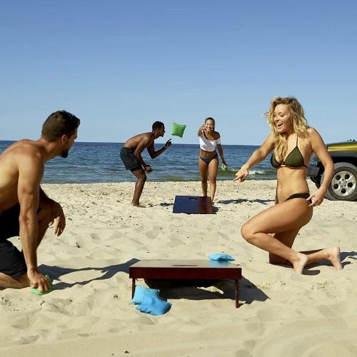 couple playing cornhole on beach