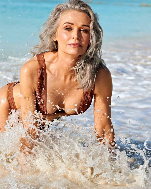 Silver haired lady playing in surf